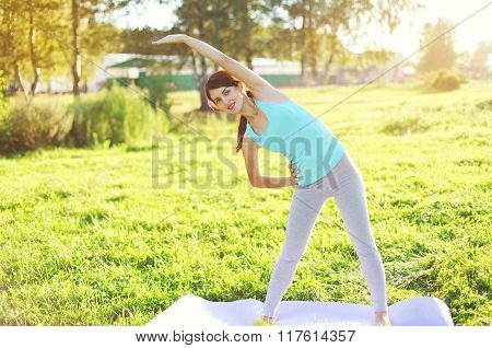 Young Woman Doing Yoga Stretching Exercises On Grass In Sunny Summer Day