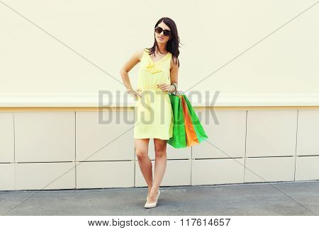 Beautiful Brunette Woman Wearing A Yellow Dress With Shopping Bags In City