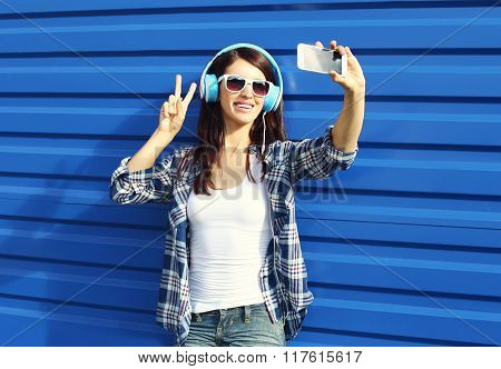 Pretty Girl Makes Self-portrait On Smartphone And Listens To Music In Headphones Over Blue Backgroun