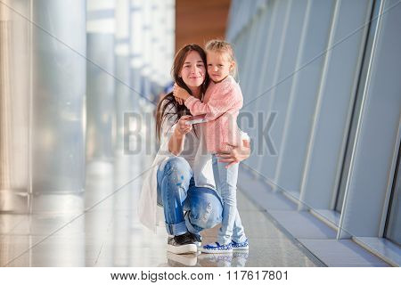 Mother and little girl in airport waiting for boarding