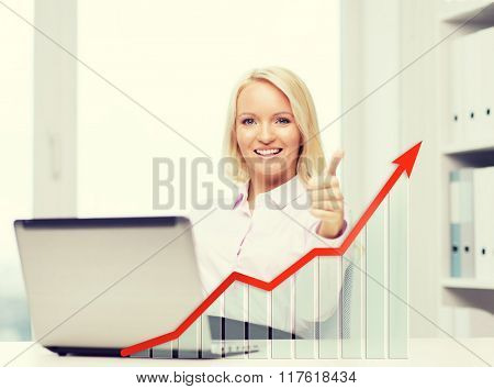 business, success, people, gesture and technology concept - smiling businesswoman showing thumbs up with laptop computer and growing chart in office