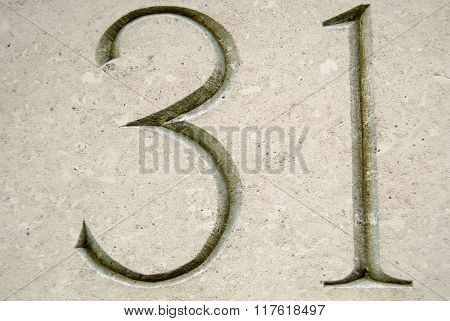 Number thirty one carved into stone on the outside of a building in the City of London. Viewed from a public pavement