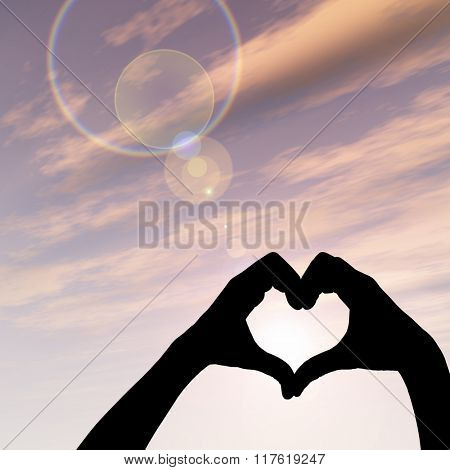 Concept or conceptual heart shape or symbol made of human or woman and man hand silhouette over a sky at sunset background