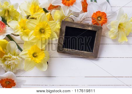 Border From  Yellow, Orange And White Spring Flowers And Empty Blackboard On White  Wooden Planks.