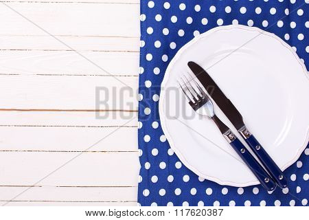 Knife And Fork On White Plate On Blue Dotted Napkin On White  Wooden Background.