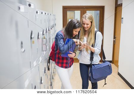Students with smartphone near lockers at university