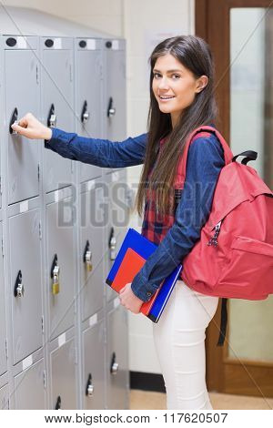 Smiling student opening locker at university