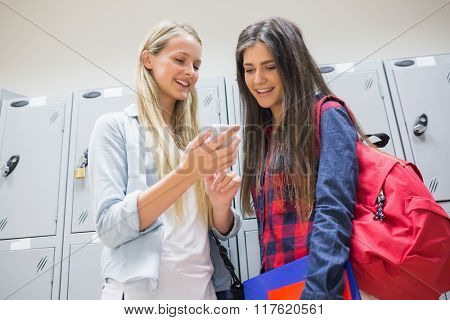 Smiling students using smartphone near lockers at university
