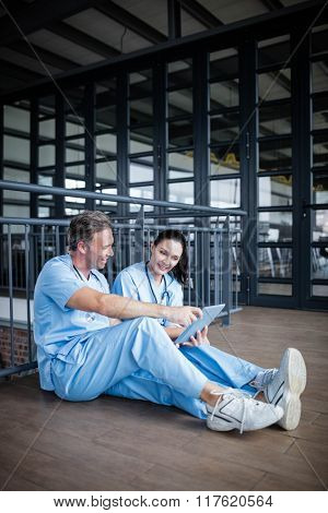 Two nurses sitting on floor and talking at the hospital