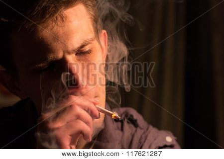 Young Man Alone Smokes Cigarettes