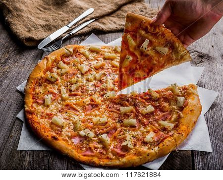 Hand Taking A Slice Hawaiian Pizza On A Old Wooden Table
