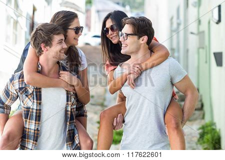 Hip men giving piggy back to their girlfriends on the street