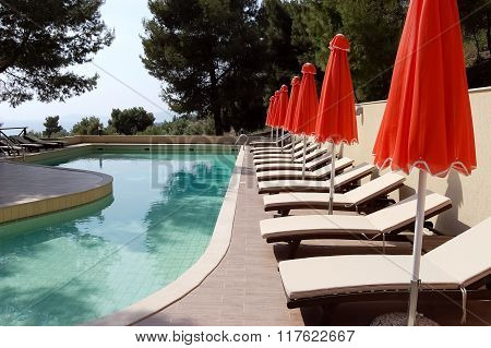 Pool And Red Umbrellas In Greek Hotel.