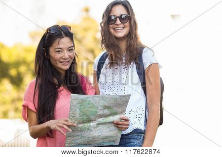 Hip friends holding map and looking at the camera outdoors