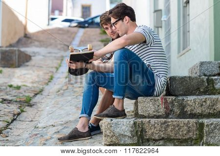 Hip men sitting on steps and holding skateboard in the city
