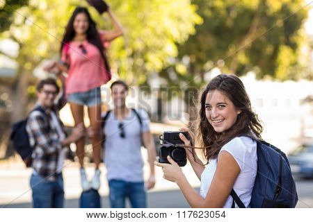 Hip woman taking picture of her friends in the city