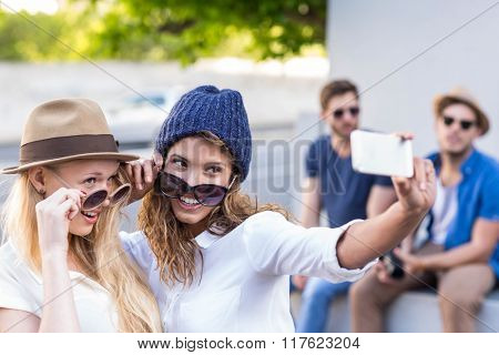 Hip friends taking selfies in the streets