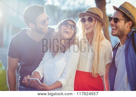 Hip friends checking at smartphone on the streets