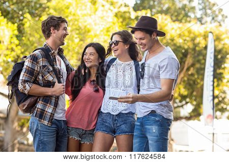 Hip friends looking at smartphone in the streets
