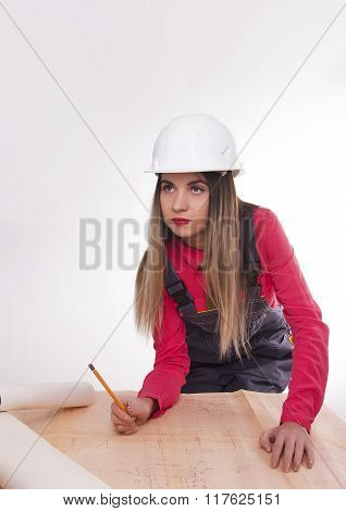 Female civil engineer standing next to the table, she bent over blueprints. young female architect