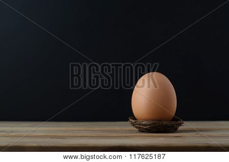 Brown Egg In Nest On Wooden Table With Black Background