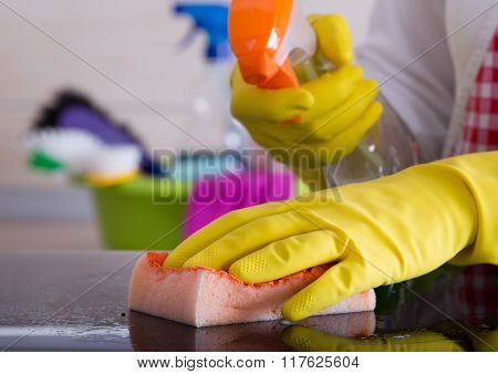 Woman Cleaning With Sponge And Liquid Detergent