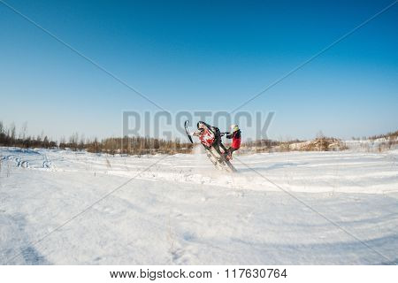 man and fast action snowmobile jumping