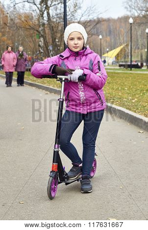 Schoolgirl posing with a scooter in the park