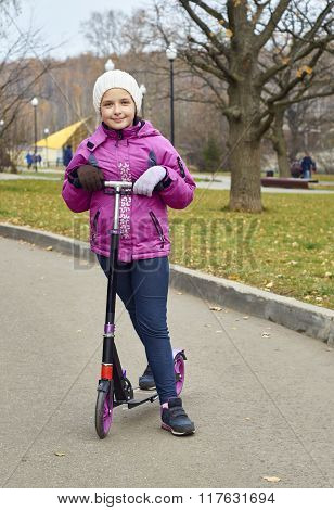 Portrait of a girl with a scooter outdoors