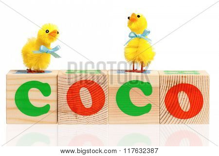 Coco word formed by colorful wooden alphabet blocks, isolated on white background