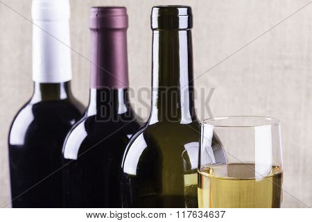 glass of white wine on the background bottles