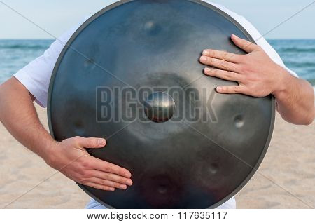 Busker on the sand beach and holding a handpan or hang with sea On Background. The Hang is tradition