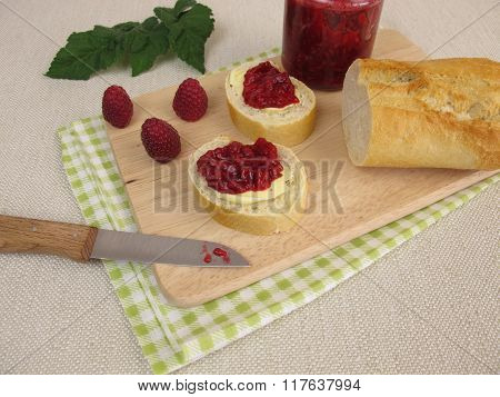 Breakfast with raspberry jam and baguette