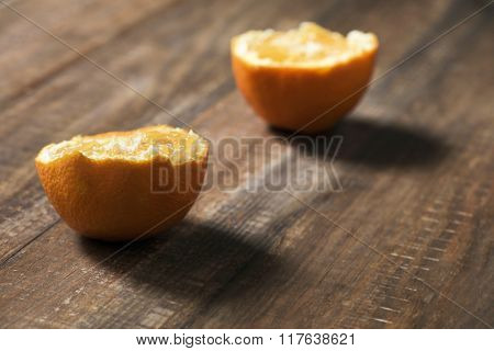 closeup of an orange cut in half on a dark wooden table