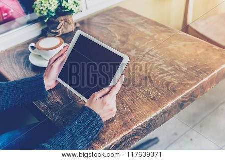 Woman Using Tablet In Coffee Shop With Vintage Tone.