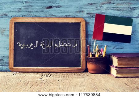a chalkboard with the question do you speak Arabic? written in Arabic, a pot with pencils, some books and the flag of the United Arab Emirates, on a wooden desk