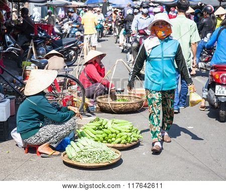 Women are selling greens at the crowded market street