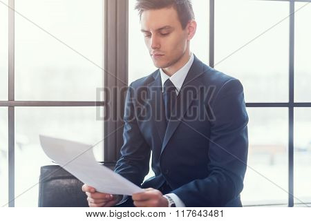 Businessman sitting in office reading contract documents