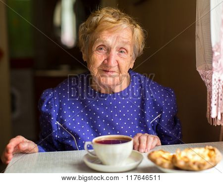 An elderly woman sitting at the table and drinking tea.
