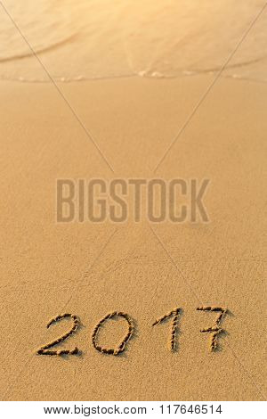 2017 - inscription on sand beach with the soft wave.