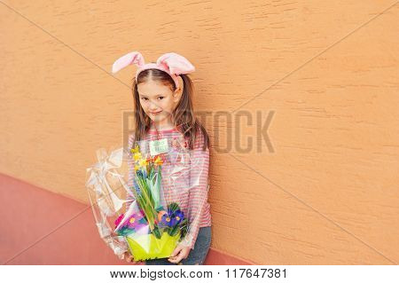 Cute little girl wearing rabbit ears, holding spring flowers in a pot with the sign happy easter