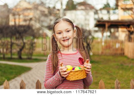 Outdoor portrait of a cute little girl with easter eggs