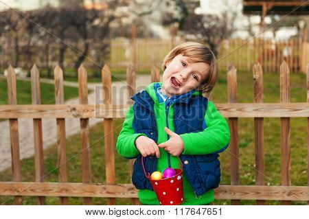 Cute little boy with bucket full of colorful easter eggs