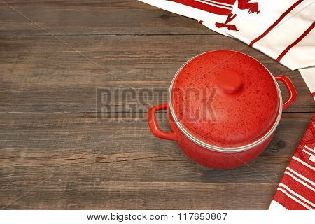 Covered Red Saucepan  And White Tablecloth On Wood Table Background