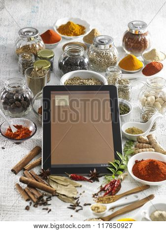 Digital tablet in the middle of the spices.
