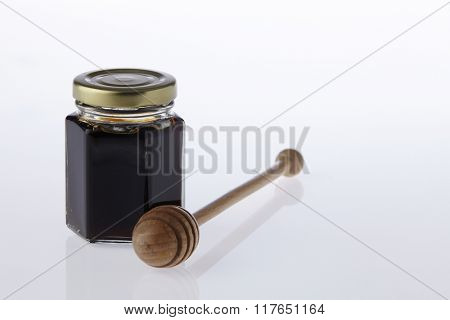 honey dipper and bottle of honey by the side