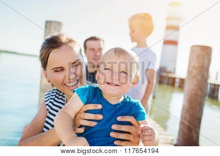 Family on the pier at the lighthouse, sunny summer day