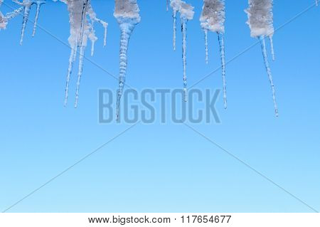 Spring thaw ice icicles on blue sky background.