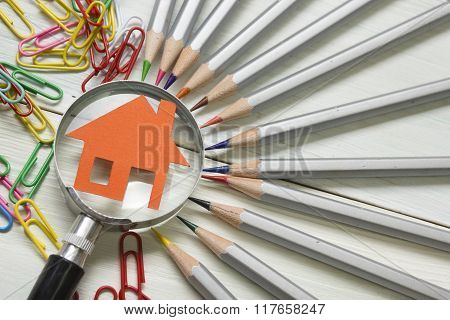 Real estate concept - magnifying glass, pencils and model house on wooden table.