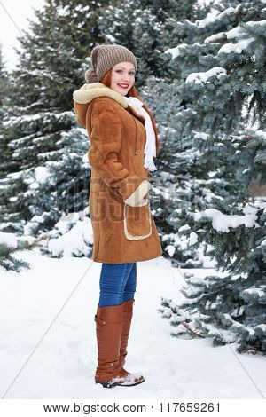 Girl posing in winter park at day. Snowy fir trees. Redhead woman full length.